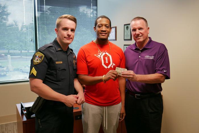AnhRandrell Lewis (người mặc áo đỏ) trả lại số tiền nhặt được cho cảnh sát.