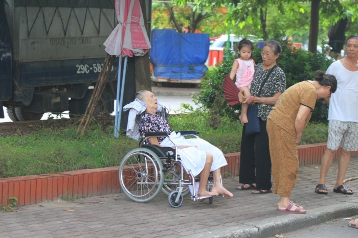 Một cụ bà đi xe lăn kịp thời được đưa xuống tầng 1.