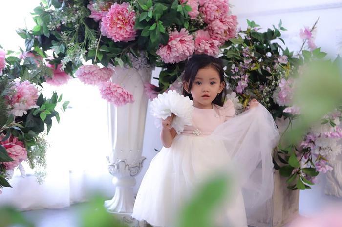 Cô bé Kem với gương mặt xinh xắn, tay cầm bó hoa trắng, mặc chiếc váy màu hồng bồng bềnh đứng trong khung cảnh cũng đầy những chậu hoa hồng xinh đẹp