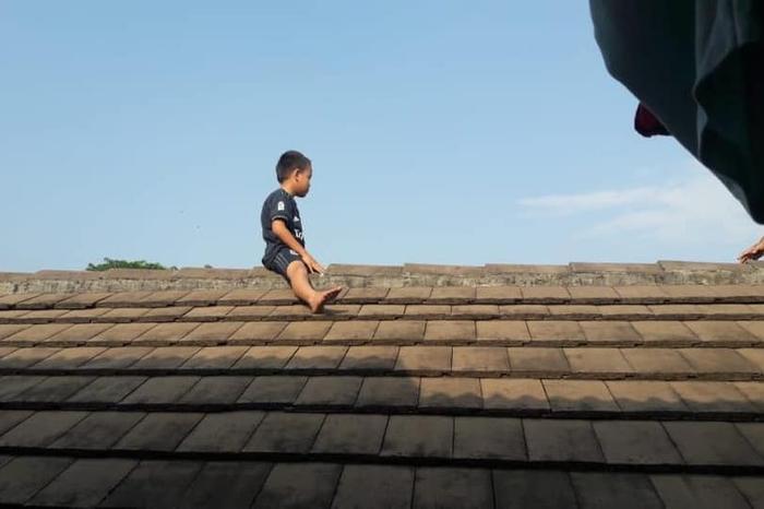 Cậu bé sợ hãi trốn lên mái phòng khám.