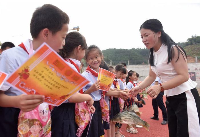 Giáo viên trao phần thưởng là những con cá chép sống cho các học sinh xuất sắc. Ảnh: China Plus
