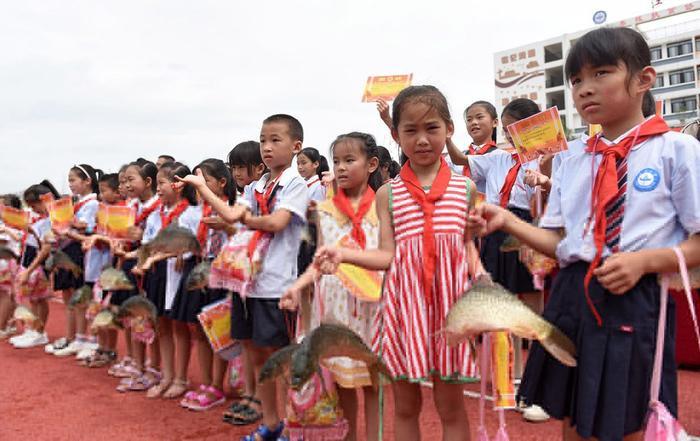 Học sinh cầm phần thưởng là một con cá chép và túi thạch trong lễ tổng kết năm học. Ảnh: China Plus