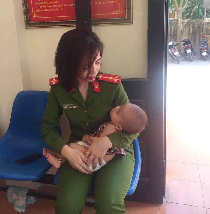 Bé gái được nữ cảnh sát cẩn thận chăm sóc.