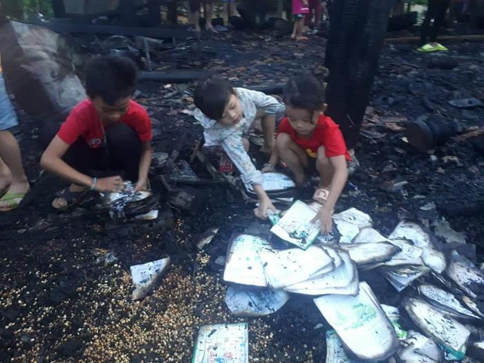 3 anh em bới đống tro tàn để nhặt tìm những trang sách không còn nguyên vẹn. Ảnh: báo Người Đưa Tin