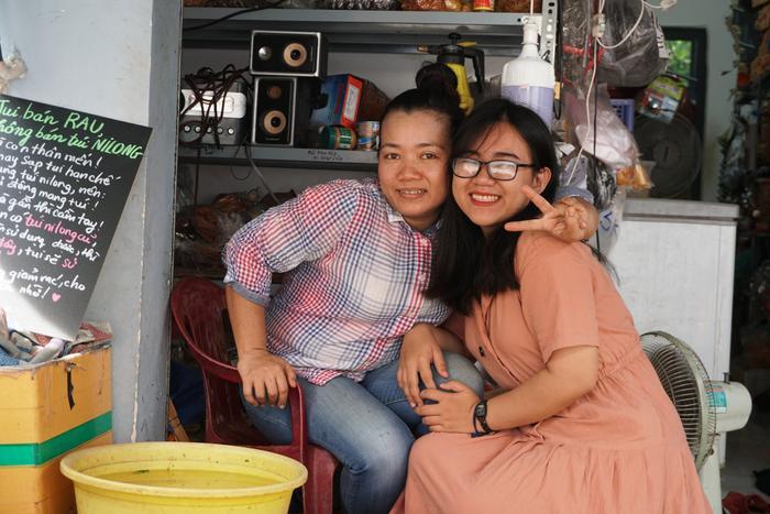 Cô bán hàng ở chợ đầu hẻm cùng tấm bảng do chính Hương viết ra.