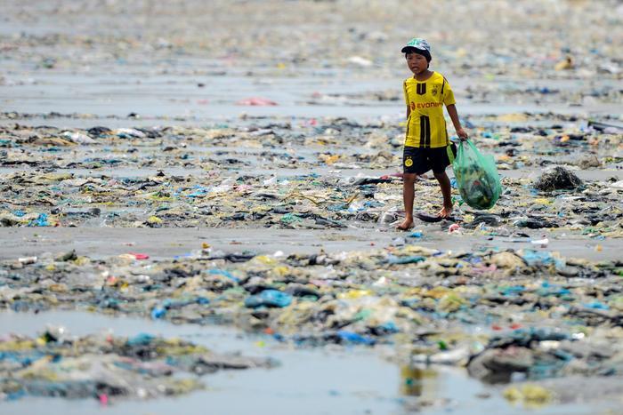 Một cậu bé bước trên bờ biển tại cửa sông Thu Bồn (Hội An, Quảng Nam) được phủ kín bởi rác thải nhựa.