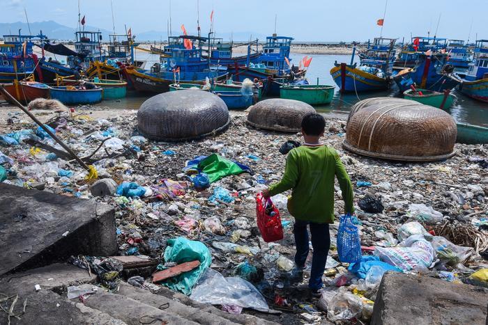 Một chú nhóc vượt qua bãi biển đầy rác để mang đồ lên thuyền ở thị trấn Liên Hương, huyện Tuy Phong (Bình Thuận). Buổi tối ở đây có những chú chuột cống to kinh hoàng, chúng kiếm ăn quanh đống rác khiến người cũng phải sợ.