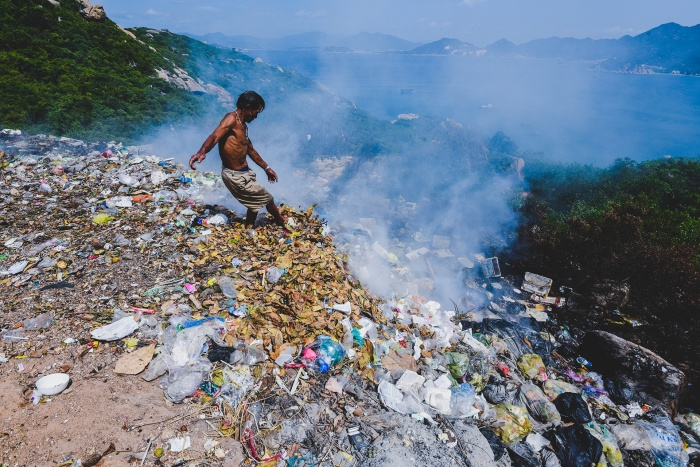 Ông Nguyễn Lương, người phụ trách lò đốt rác ở đảo Bình Ba (Khánh Hòa) đang dùng chân đẩy rác. Xung quay cấy cối chết khô. Đây là một sườn dốc của đảo, phía dưới là bãi tắm và là vịnh nuôi tôm hùm, thuỷ hải sản.