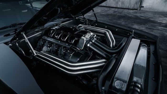 Nằm bên dưới nắp ca-pô, ngay cả khoang động cơ cũng được trang trí bằng các tấm carbon bao xung quanh cỗ động cơV8 9.0L Mercury Racing tăng áp kép, cho công suất 1.650 mã lực kết hợp cùng hộp số sàn Tremec 6 cấp.(Ảnh: Motor1)