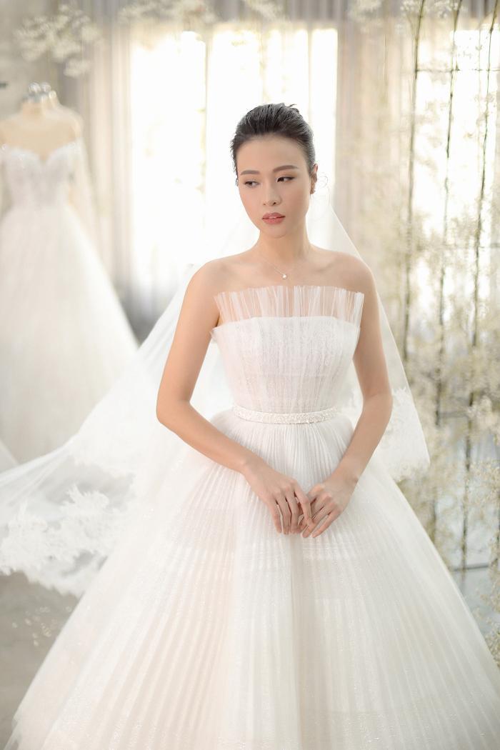 Điểm đặc biệt của chiếc đầm cưới chính nằm ở kỹ thuật dựng phom corset giúp vòng eo nhỏ nhất có thể, đồng thời ở phần ngực áo, NTK chọn lựa dáng váy quây để tôn lên vòng một của cô dâu, nhấn nhá thêm lớp lưới dập ly khéo léo làm tăng thêm phần nền nã, dịu dàng.