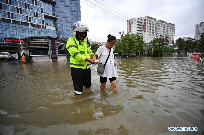 Cảnh sát giao thông đang giúp một phụ nữ mang thai lội qua con đường ngập nước ở thành phố Hải Khẩu, tỉnh Hải Nam.