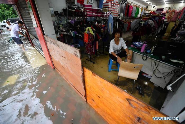 Các cửa hàng dọc theo đường Longhua ở thành phố Hải Khẩu bị nước mưa tràn vào trong hôm 1/8.