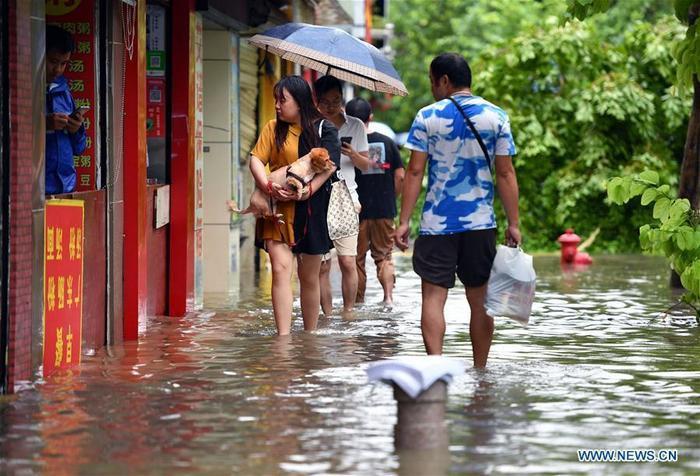Người dân lội qua đoạn đường Longhua ngập nước.