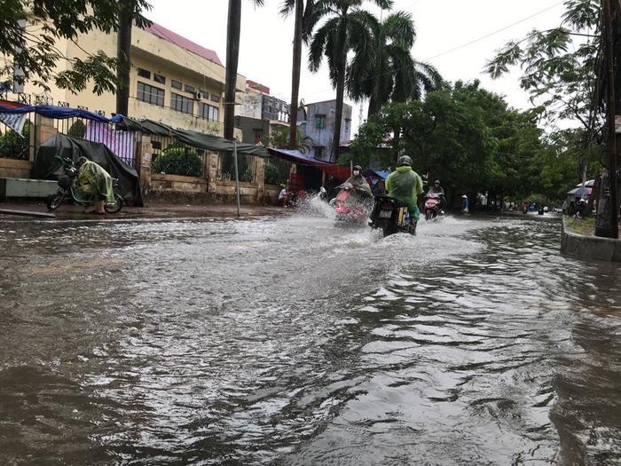 Tại tuyến đường Nguyễn Bình đến gần trưa cùng ngày nước vẫn ngập khá sâu khiến việc đi lại của người dân gặp nhiều khó khăn.
