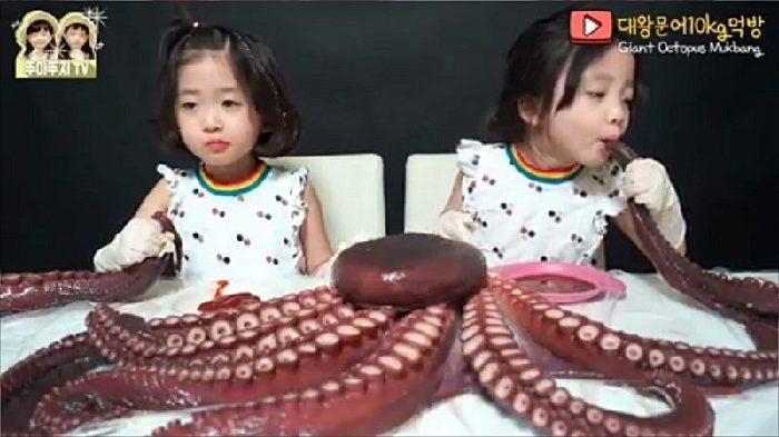 Cặp song sinh Hàn Quốc liên tục rên rỉ khi phải cố nhai, nuốt con bạch tuộc khổng lồ.