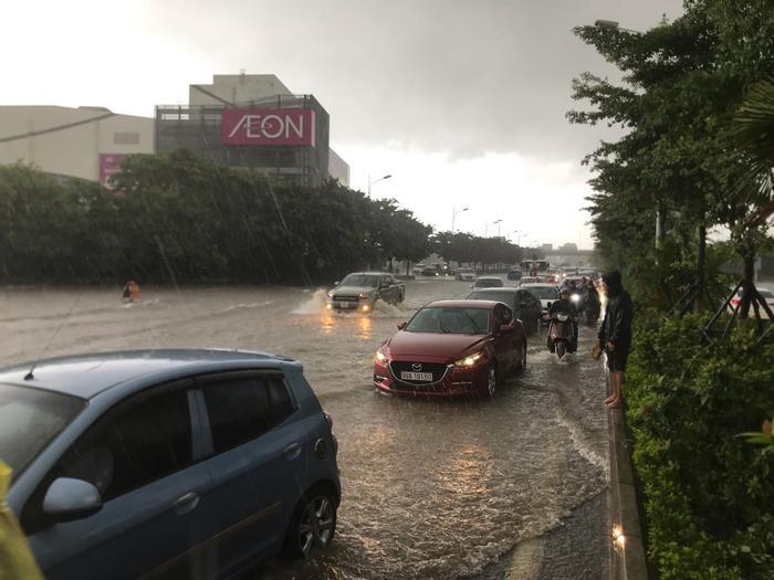 """Hình ảnh ghi nhận từ AEON Mall, quận Long Biên (Hà Nội),nước lũ """"bao vây"""" khiến các phương tiện di chuyển khó khăn, nhiều ô tô chết máy."""