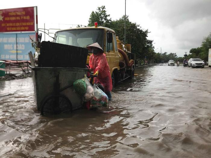 Lực lượng công nhân vệ sinh môi trường vất vả đẩy xe rác qua con đường ngập sâu trong nước.
