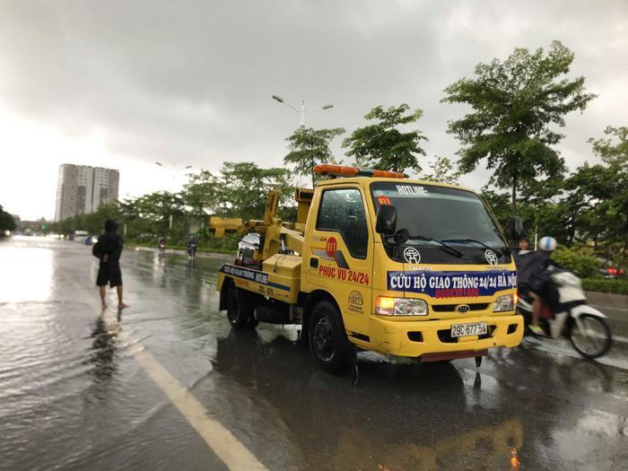 """Do mưa lớn ngập sâu khiến nhiều phương tiện trong đó có cả ô tô, xe máy không thể di chuyển. Đây cũng là cơ hội để dịch vụ """"giải cứu"""" ô tô chết máy hốt bạc."""