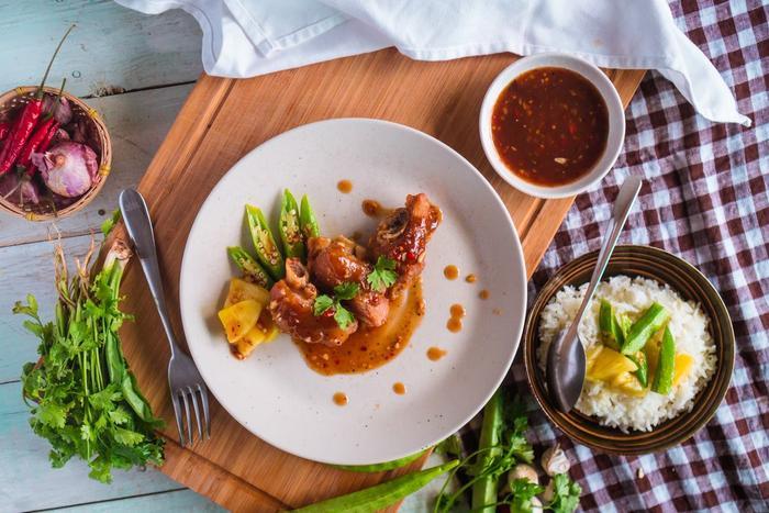 Hương vị của móng heo vàng giòn được dậy lên bởi vị chua cay của sốt Thái. Tất cả được cân bằng bởi vị ngọt khi sauté thơm và đậu bắp.