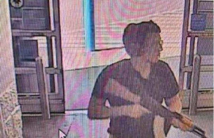 Tên sát nhân lăm le khẩu súng trường khi tiến vào siêu thị.