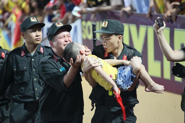 Hình ảnh đại uý Giảng chịu đau để cháu bé lên cơn co giật cắn vào tay.