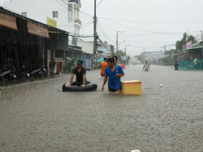 Mưa lớn khiến nước ngập sâu, gây khó khăn trong việc di chuyển. Ảnh: Tuổi Trẻ
