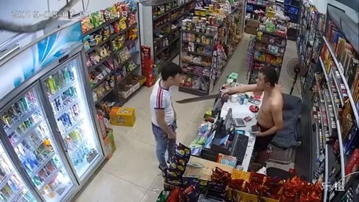 Tên cướp bị ông chủ cửa hàng chĩa dao vào người đe dọa.
