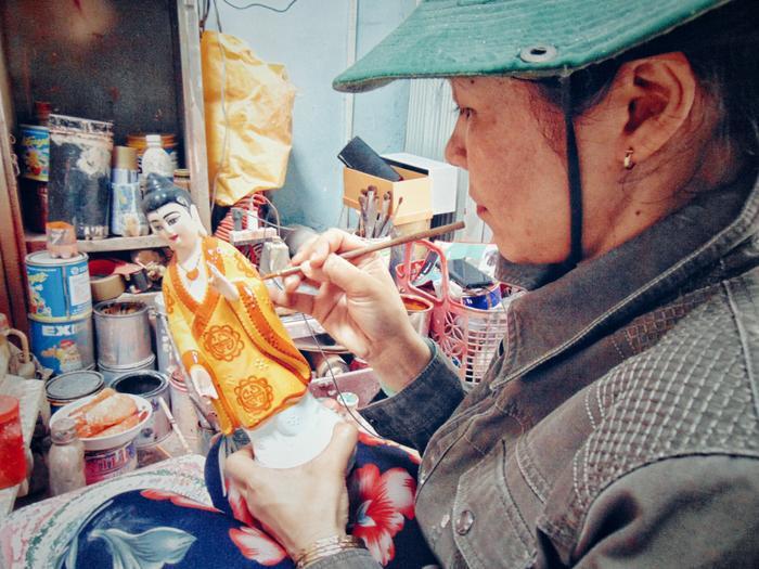 Chị Ánh đang sơn một bức tượng, đây cũng là khâu quan trọng trong việc tạo nên hồn cho tôn tượng,