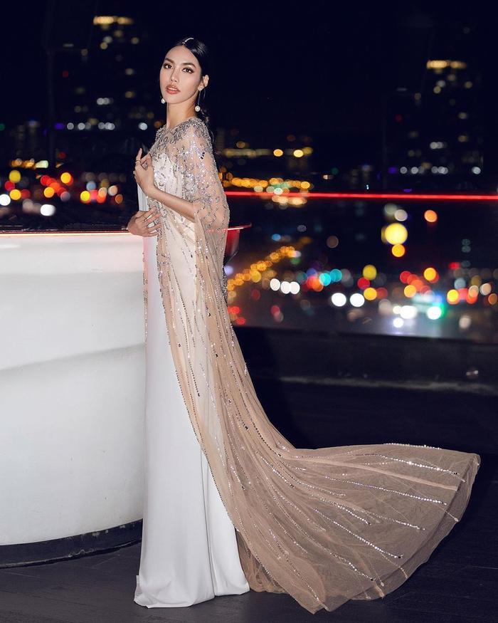 Đầm trắng với áo cape vải xuyên thấu tăng độ quyền lực mà đánh lừa thị giác