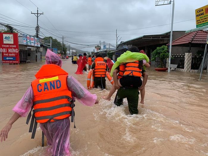 Lực lượng chức năng giúp người dân di chuyển khỏi vùng ngập sâu. Ảnh: VietNamNet