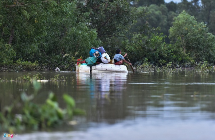 Nhiều hộ dân tranh thủ mưa ngớt vận chuyển đồ đạc đến nơi an toàn. Ảnh: báo Zing