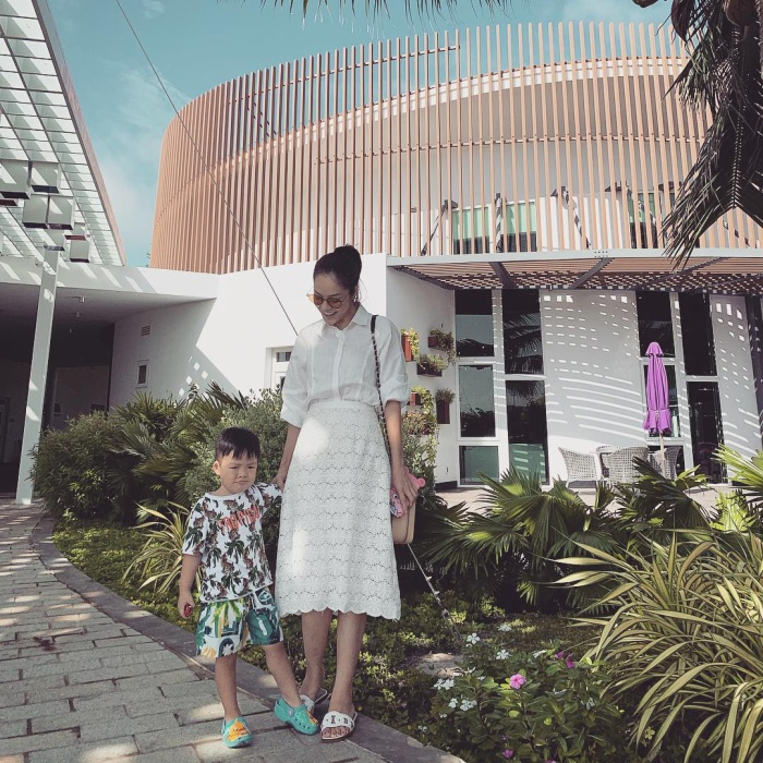 Xuống phố ngày nắng cùng con trai, Dương Cẩm Lynh mix cho mình outfit đơn giản, nhã nhặn nhưng vẫn rất hợp thời trang gồm áo và chân váy theo tông trắng nhã nhặn.