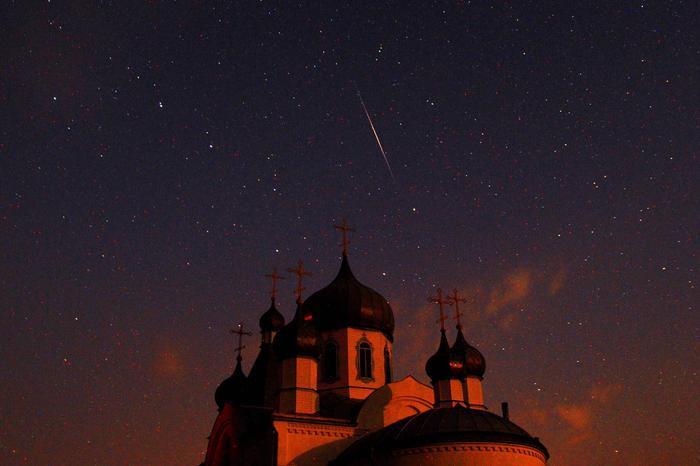 Bên trên nóc một nhà thờ Chính Thống Giáo ở Belarus, sao băng Perseid vút nhanh qua bầu trời. Ảnh: Sergei Gapon/AFP