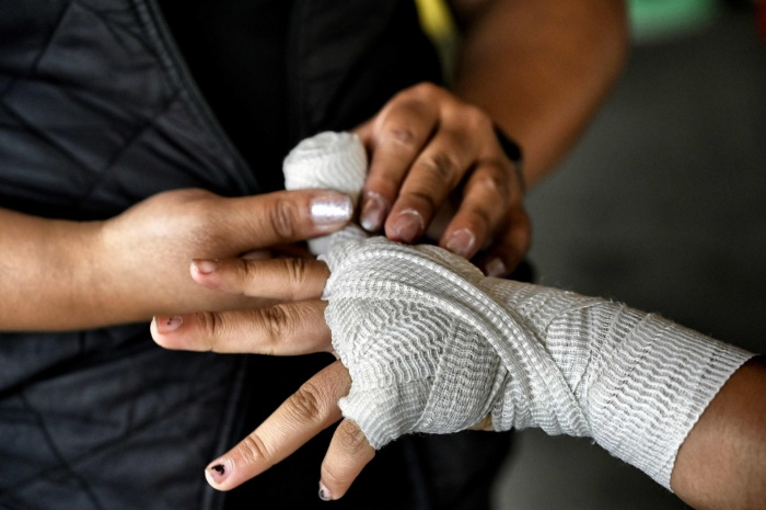 Một người mẹ đang băng tay cho con trai mình tại phòng tập trước khi cậu bé lên võ đài để tỉ thí tập luyện.
