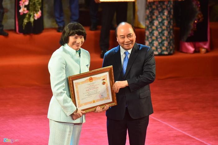 Nghệ sĩ cải lương Minh Vương nở nụ cười tươi tắn khi lên sân khấu nhận danh hiệu NSND. Trước đó, Minh Vương từng bị trượt danh hiệu này. (Ảnh: Zing.vn)