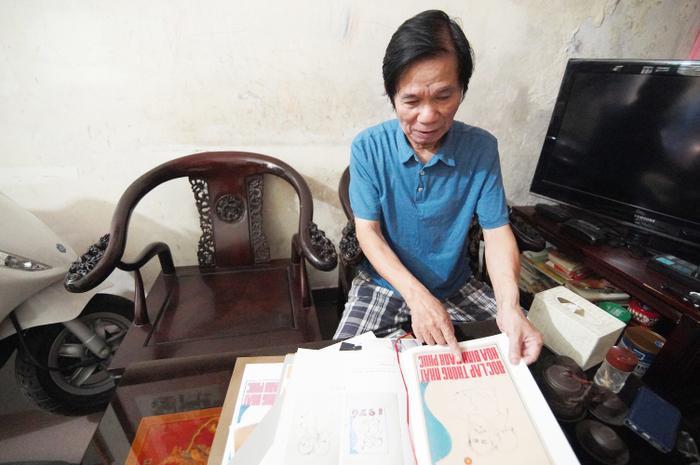 Hoạ sĩ Trần Từ Thành bên bức tranh vẽ chân dung Bác Hồ và em bé.
