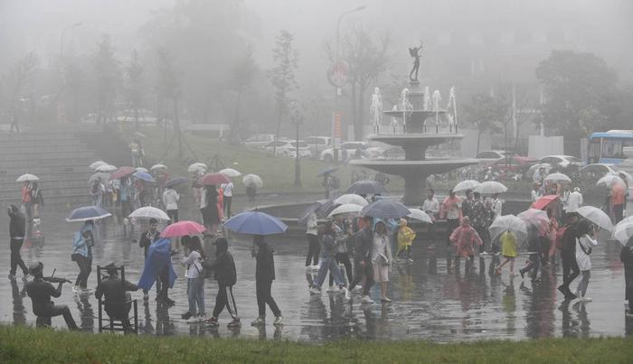"""Khách du lịch tại quảng trường trung tâm thị trấn Tam Đảo. Anh Trần Viết Hùng (Phú Thọ), một du khách tới đây nghỉ lễ, nói: """"Tôi và gia đình đã đặt xe cùng phòng khách sạn cách đây hơn một tuần nên dù mưa vẫn cố gắng đi""""."""