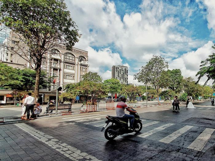 """Phố đi bộ Nguyễn Huệ không còn """"nguy hiểm"""" bởi dòng xe lưu thông, các cặp đôi đứng giữa đường chụp ảnh cưới thoải mái."""