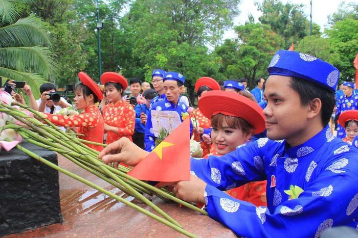 Các cặp đôi dâng hoa tại tượng đài Bác Hồ. Ảnh: báo Tiền Phong