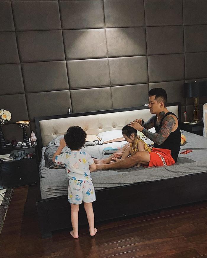 Bà xã Tuấn Hưng đã lén chụp lại khoảnh khắc chồng đang ngồi trên giường chăm chú buộc tóc cho con gái vào buổi sáng, bên cạnh là cậu con trai đang đứng chơi