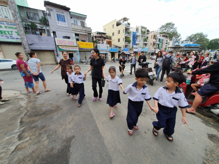 Ngày đầu tiên đi học, bà nội và mẹ dẫn các bé đến trường.
