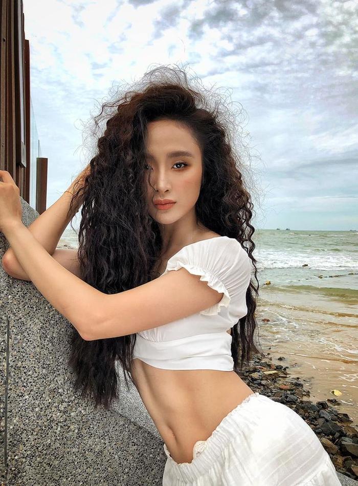 Để tóc xoăn xù và kết hợp với lối trang điểm sắc sảo, Angela Phương Trinh trông không khác gì gái Tây đang khoe dáng bên bờ biển