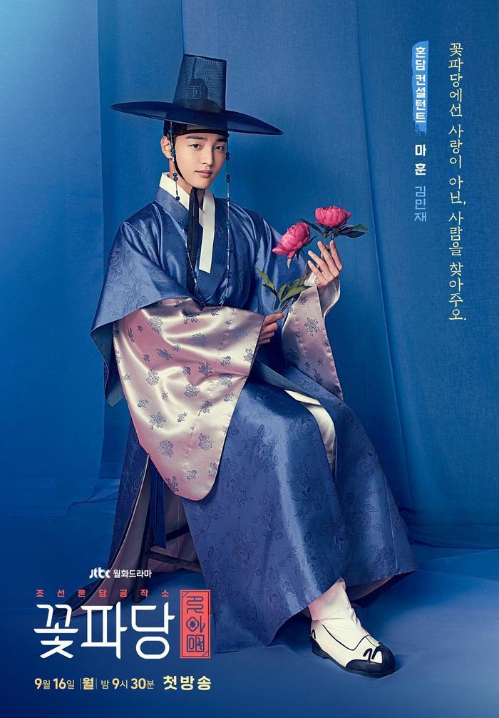 """Nhân vật Ma Hoon do diễn viên Kim Min Jae thủ vai là người làm mai mối đỉnh nhất kinh thành nhưng tính cách cũng """"khó ở"""" không kém. Poster của Ma Hoon mang màu xanh thẫm chủ đạo, trên tay anh là một nhành mẫu đơn, """"tôn chỉ"""" làm việc của Ma Hoon là: """"Tại Biệt đội hoa hòe, chúng tôi giúp bạn tìm người, không tìm tình yêu""""."""
