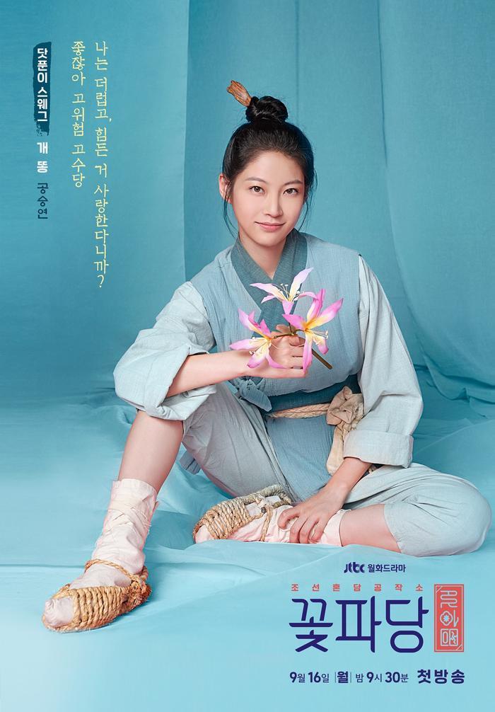 """Poster của Gae Ddong có màu xanh bạc hà mát dịu, loài hoa biểu trưng là hoa ly: """"Tôi thích những công việc bẩn thỉu và khó khăn thì sao nào. Rủi ro càng cao, đãi ngộ càng lớn""""."""