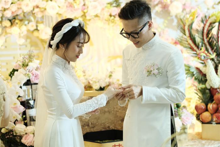 """Cô dâu Minh Anh sẽ """"theo chàng về dinh"""" trong chiếc áo dài lụa trắng muốt theo phong cách truyền thống của NTK Phạm Đăng Anh Thư. Chiếc áo dài đính ngọc trai làm điểm nhấn ở phần cổ càng tôn lên nét mảnh mai, trong trẻo của cô dâu.Minh Anh và chú rể Tâm Nguyễn nắm chặt tay, cười rạng rỡ khi thực hiện nghi thức của lễ cưới trước sự chứng kiến của người thân của cặp đôi và bạn bè."""