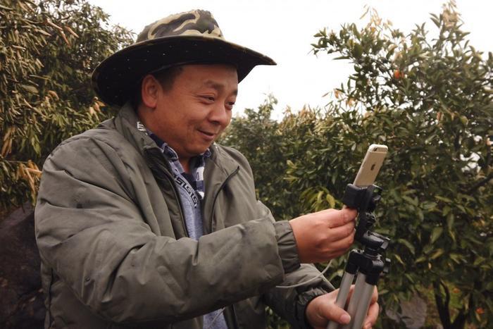 Zhong Haihui đang dùng một chiếc iPhone 6, tripod và sạc dự phòng để livestreaming trên Kuaishou và Taobao. (Ảnh: SCMP)