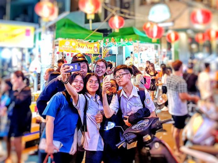 Một nhóm các bạn trẻ sau khi đi học về cũng tranh thủ ghé sang phố để chụp ảnh lưu niệm.