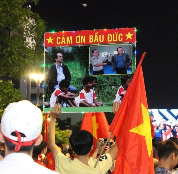 Người hâm mộ Việt Nam cầm ảnh bầu Đức ra đường ăn mừng để cảm ơn về sự đóng góp thầm lặng và lớn lao cho bóng đá nước nhà.