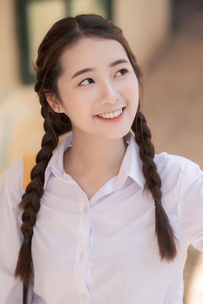 Trong bộ đồng phục trắng giản dị, mái tóc thắt bím đặc trưng của tuổi học trò, Quỳnh Suri thu hút ánh nhìn của bất kì ai bắt gặp.