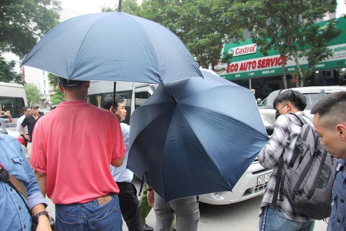 Lúc này một số người của trường Gateway cầm ô che lại chiếc xe ô tô.